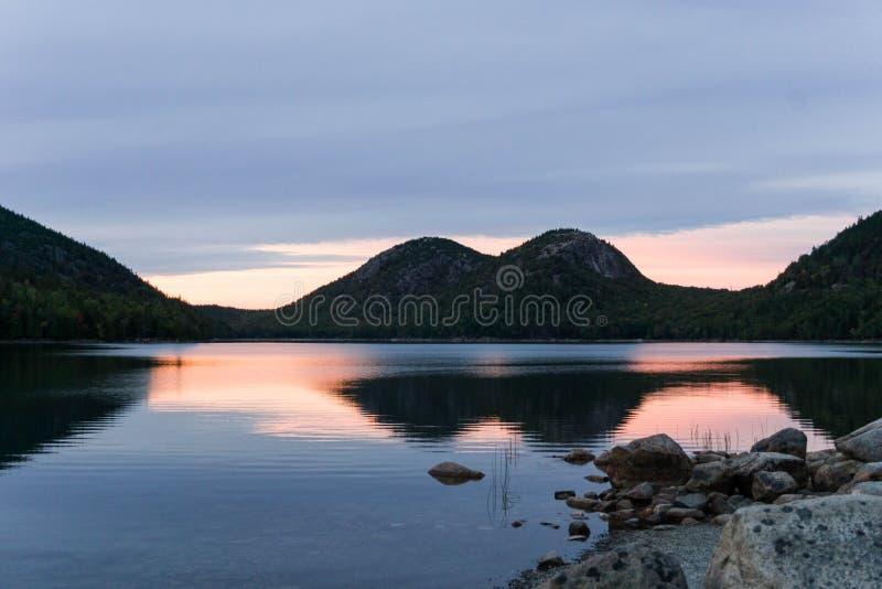Pond com juncos e rochas e montes florestados no fundo imagens de stock royalty free