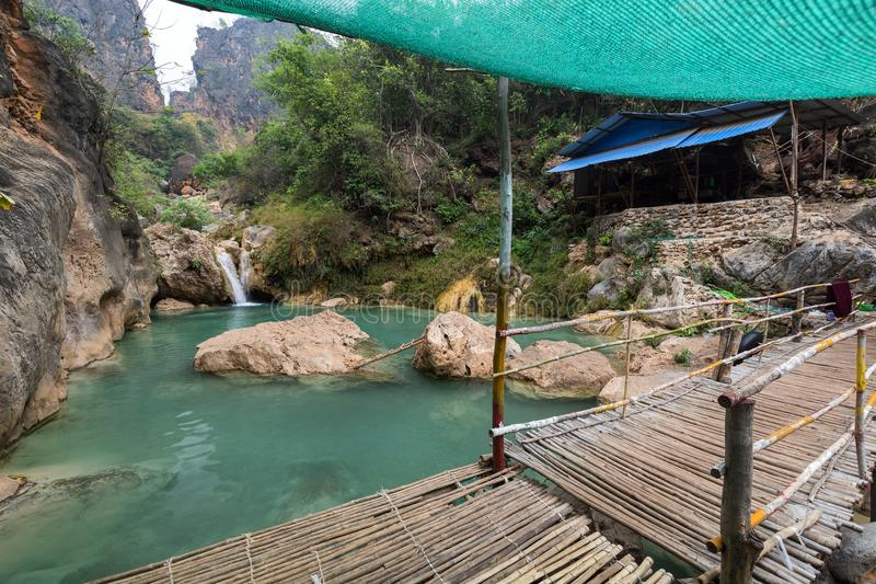 Pond at the Deed Doat Waterfalls in Myanmar. Rocks, pond, a small waterfall and simple wooden shack at the Deed Doat Waterfalls near Mandalay in Myanmar Burma royalty free stock image
