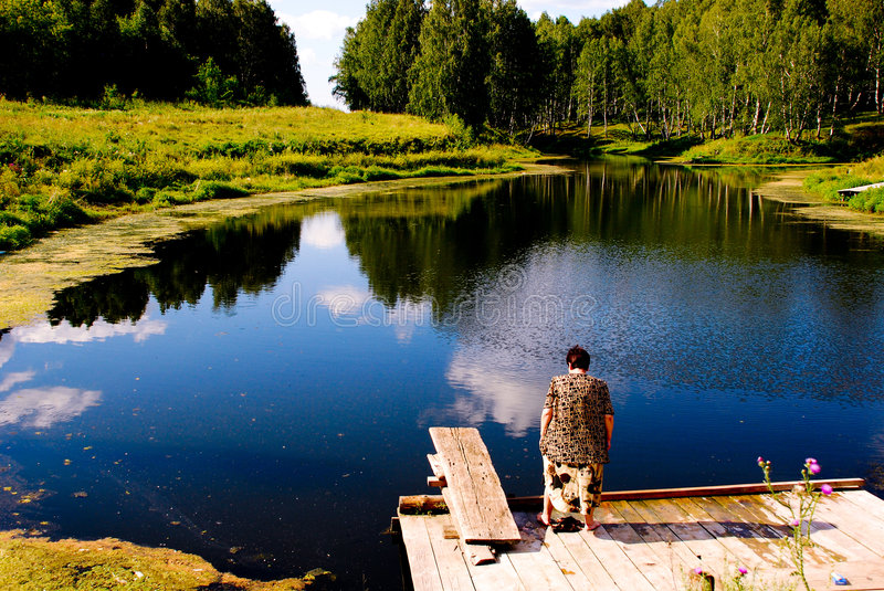 Pond with granny. A small pond and a lot of grass royalty free stock images