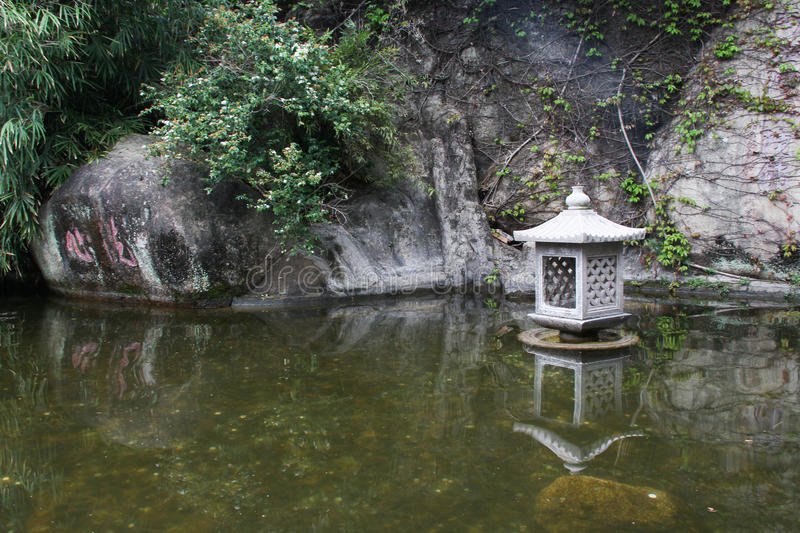 Pond and lamp in Nanputuo Temple in Xiamen city, China. Pond and lamp in Nanputuo Buddhist Temple in Xiamen city, southeast China. The temple has a history of royalty free stock photography