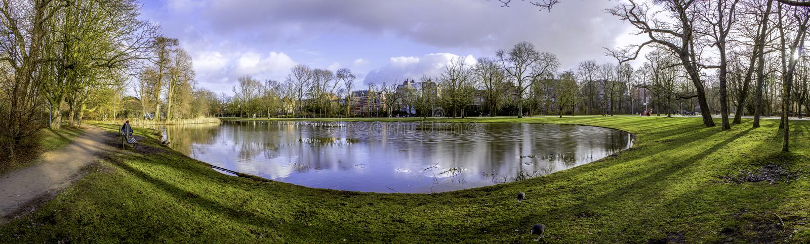 Pond panoramic landscape photo in Vondelpark, Amsterdam. Is a pu. Blic urban park of 47 hectares (120 acres), opened in 1865 and originally named the Nieuwe Park royalty free stock photo