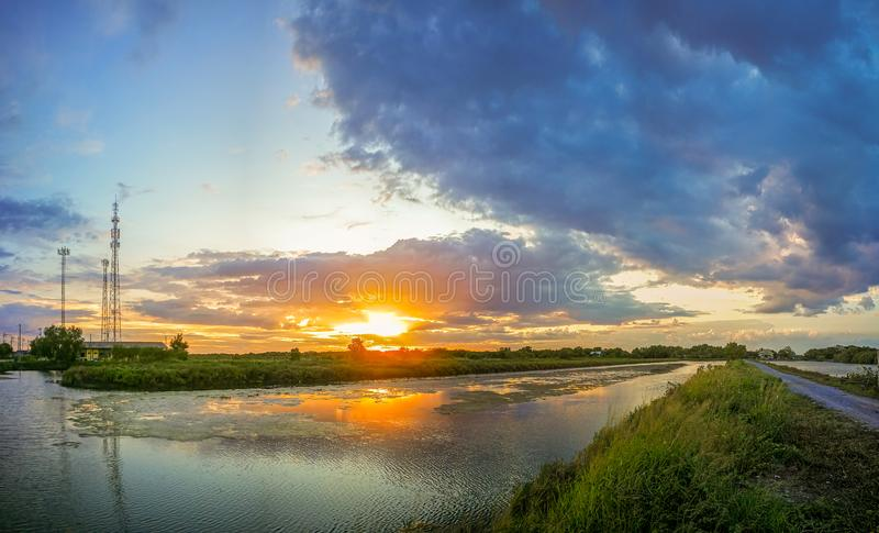 The pond reflects the light from the orange sun. The pool edge is green and yellow grass. The evening sky before the sunset is. Colorful royalty free stock photo