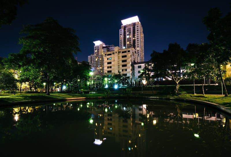 Pond at Santiphap Park and skyscrapers at night, in Bangkok, Thailand. royalty free stock photography
