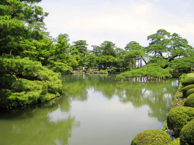 Pond surrounded by greenery in Kenrokuen garden royalty free stock photography