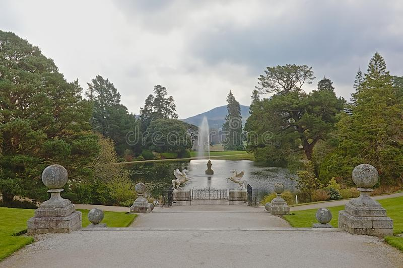 Pond with trees and in Powerscourt garden and Great sugar loaf mountain, Enneskery. Staricase to a pond with fountain and trees in the Italian garden of stock images