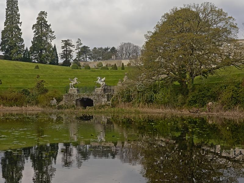 Pond with trees, winged horse statues and castle in Powerscourt garden, Enneskery. Triton lake with bridge with winged horse statues, trees and castle of stock image
