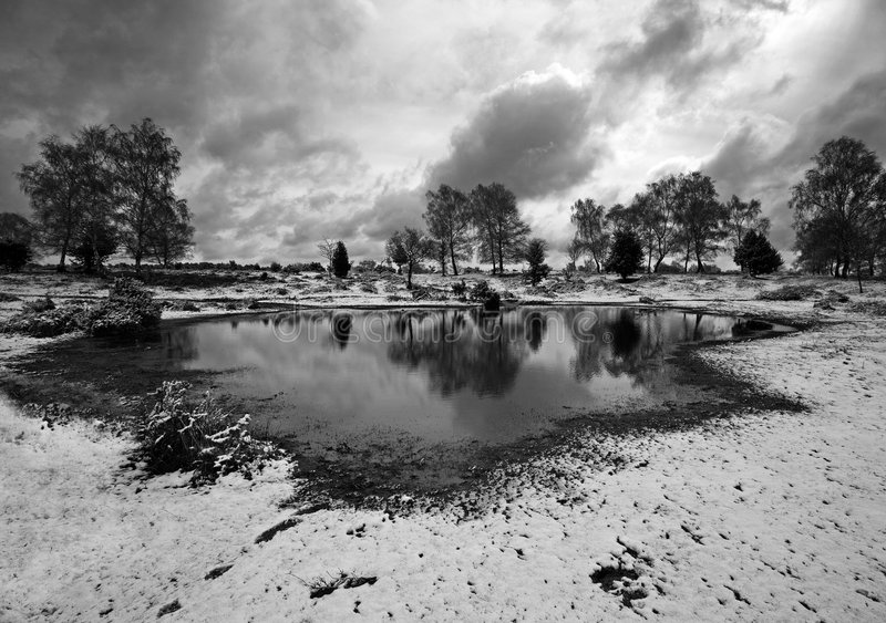 Pond in wintry countryside. Black and white scenic view of small pond in picturesque countryside under cloudscape, winter scene stock photos