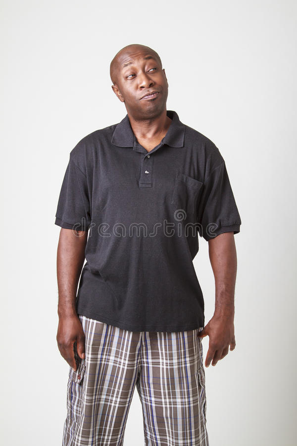 Pondering guy. Bald black man in his forty, looking to the top right corner with pondering expresison royalty free stock images