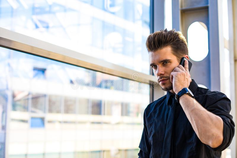 Thoughtful banker talking via cellphone. Pondering man financier in formal wear calling via smartphone while standing in business centre near window background stock image