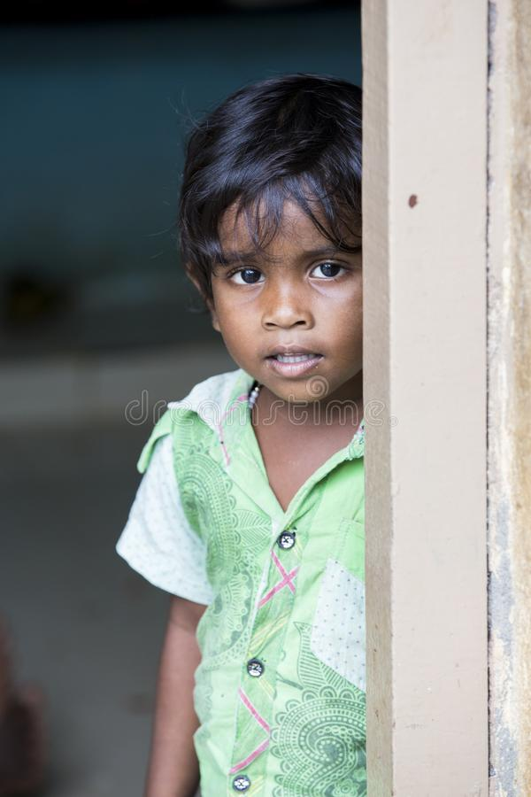 Portrait of unidentified Indian poor kid boy is smiling outddor in the street. PONDICHERY, PUDUCHERRY, TAMIL NADU, INDIA - SEPTEMBER CIRCA, 2017. Portrait of stock photos