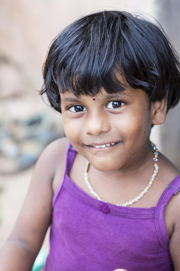 Portrait of unidentified Indian poor kid girl child is smiling outddor in the street. PONDICHERY, PUDUCHERRY, TAMIL NADU, INDIA - SEPTEMBER CIRCA, 2017. Portrait stock image
