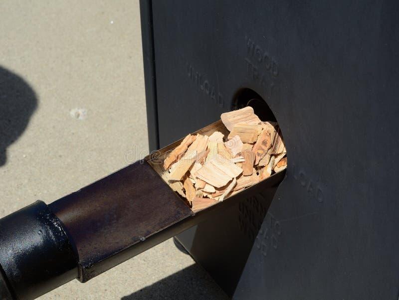 Pondo as microplaquetas de madeira em um fumador fotografia de stock