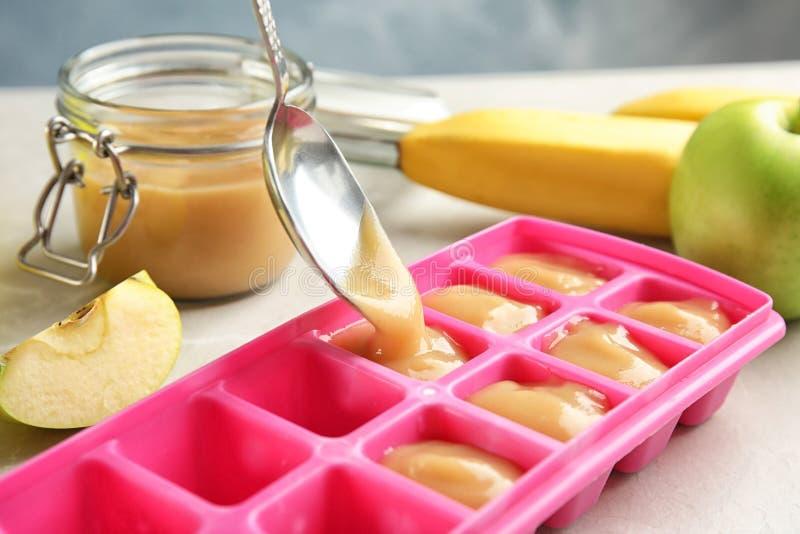 Pondo o comida para bebê saudável na bandeja do cubo de gelo, foto de stock royalty free