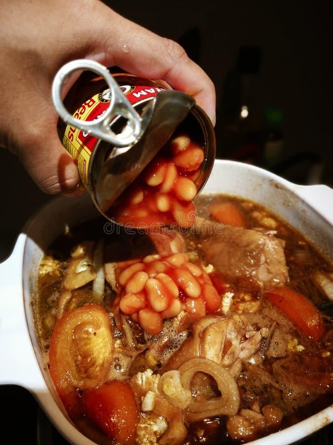 Pondo os feijões cozidos do recipiente da lata de lata no cChicken com molho de soja, ou sabido fotografia de stock