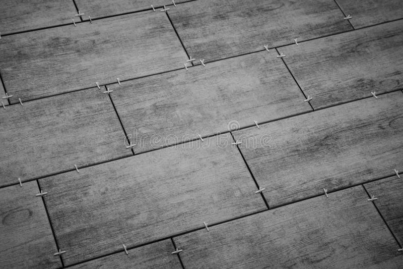 Ponendo le piastrelle di ceramica sul pavimento Fuoco selezionato Fondo fotografie stock libere da diritti