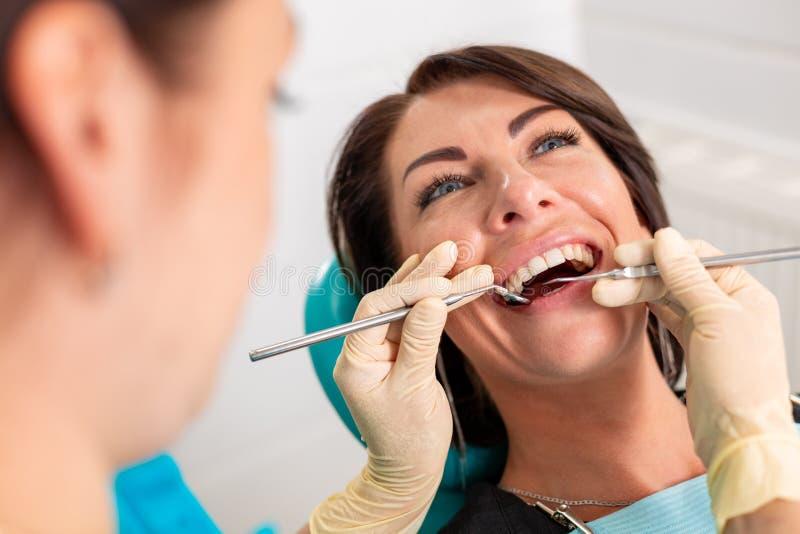 Poner apoyos dentales a los dientes del ` s de la mujer en la oficina dental Dentista examinar al paciente femenino con los apoyo imagen de archivo