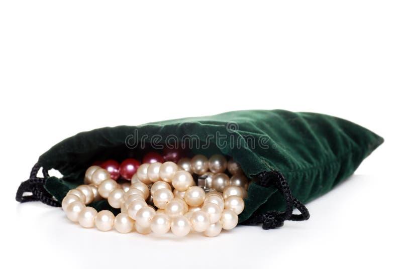 _poner crema perla en uno verde bolso fotos de archivo libres de regalías