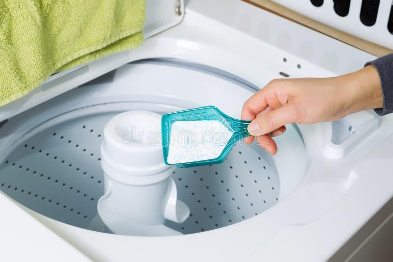 Poner el jabón en la lavadora imagen de archivo