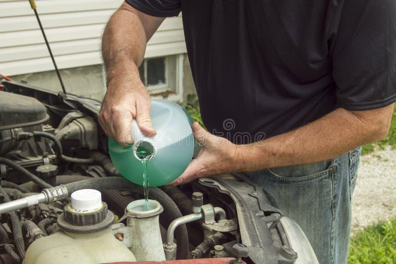 Poner el líquido del limpiaparabrisas en un coche fotografía de archivo
