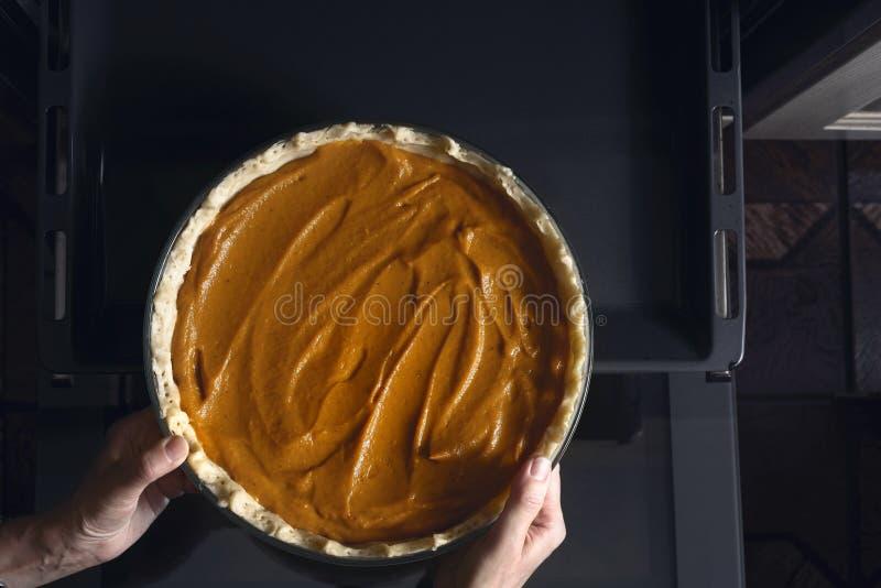Poner el pastel de calabaza en la opinión superior del horno fotos de archivo libres de regalías
