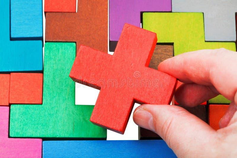Poner el pedazo cruciforme en rompecabezas de madera foto de archivo