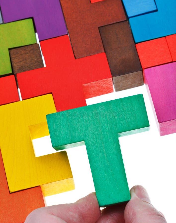Poner el pedazo T-formado en rompecabezas de madera imágenes de archivo libres de regalías