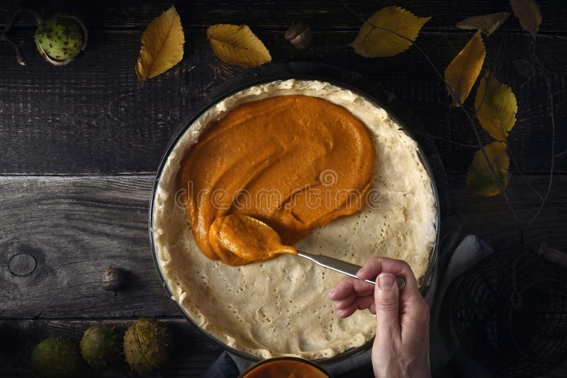 Poner el puré de la calabaza en la pasta para el pastel de calabaza en la tabla de madera foto de archivo