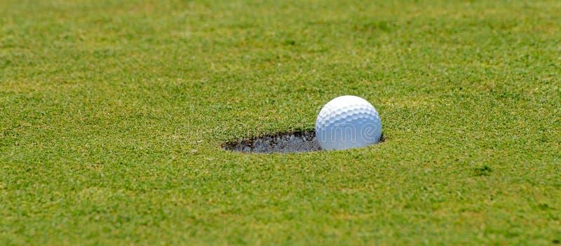 Poner la pelota de golf en el agujero fotografía de archivo libre de regalías