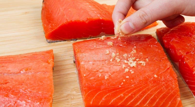 Poner la sal del mar en salmones rojos imagenes de archivo