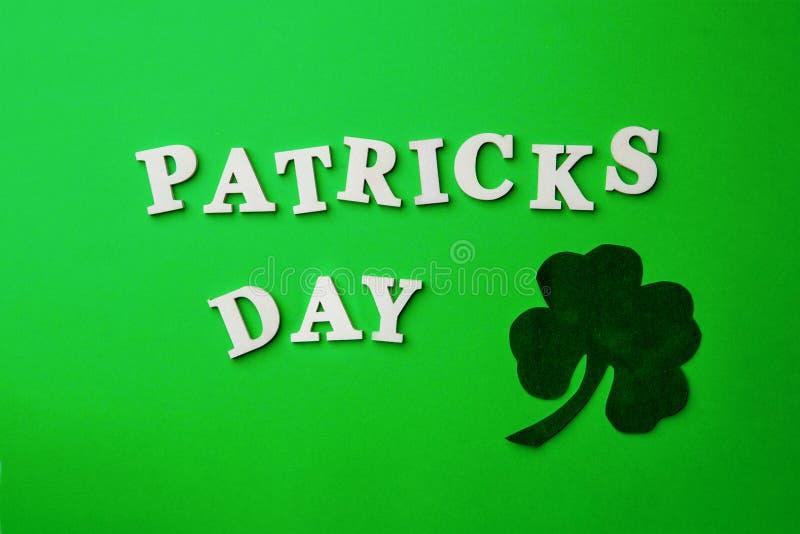 Poner letras al día de Patrick, presentado en fondo verde foto de archivo