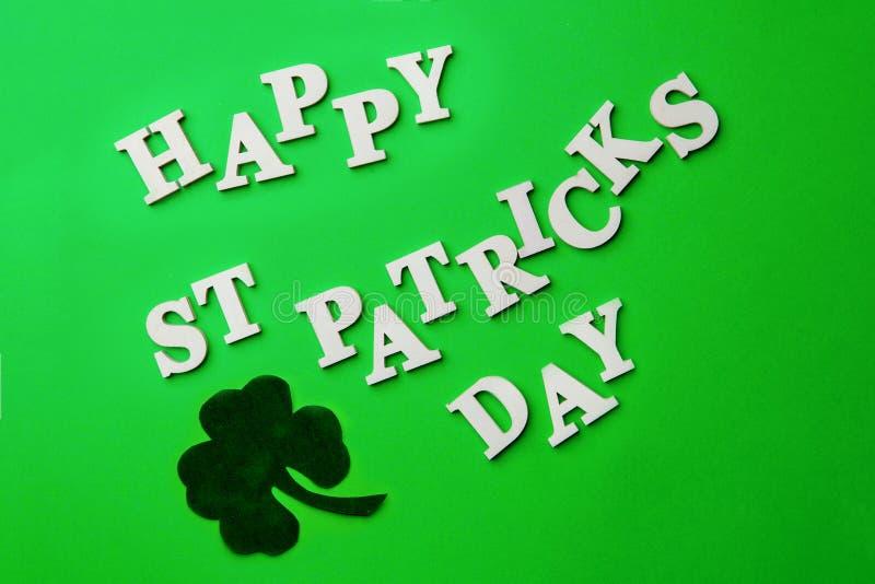 Poner letras al día de St Patrick feliz, presentado en fondo verde fotos de archivo libres de regalías