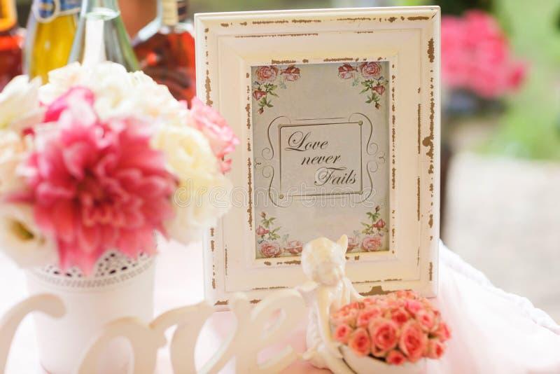 Poner letras a 'amor nunca falla' soportes en un viejo marco de madera blanco fotografía de archivo libre de regalías