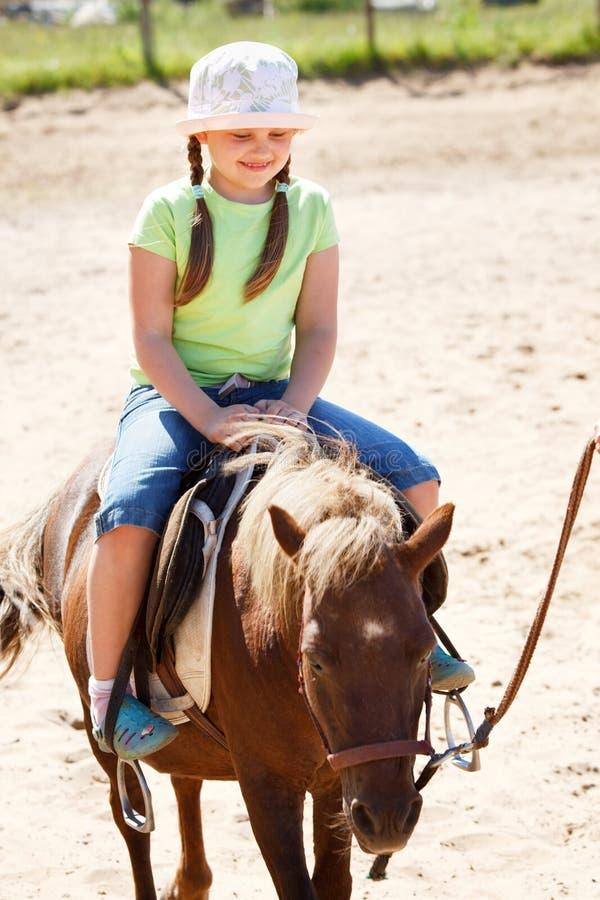 Poney d'équitation de petite fille image stock