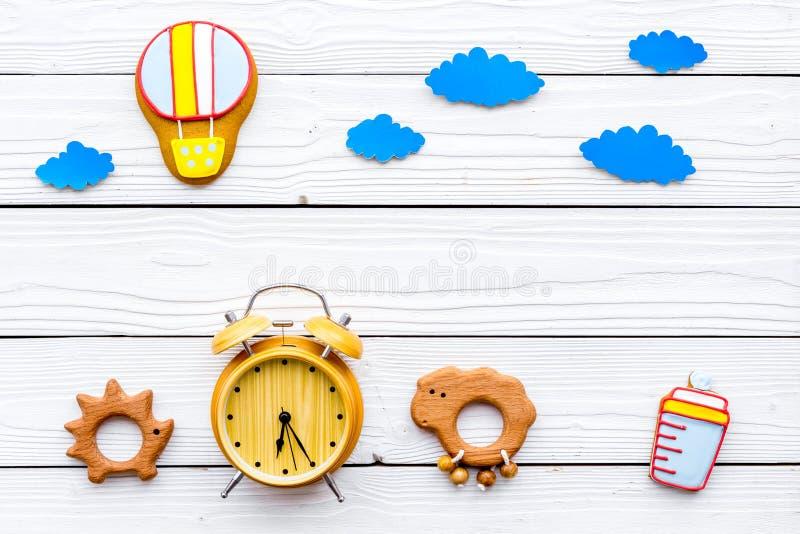 Ponga al bebé para acostar concepto Los juguetes y las charlas, accesorios del bebé, despertador, nubes de los niños en el fondo  fotografía de archivo