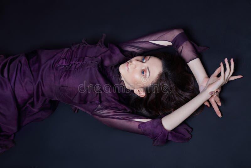 Ponga en contraste el retrato armenio de la mujer de la moda con los ojos azules grandes que mienten en el piso en un vestido púr fotos de archivo libres de regalías