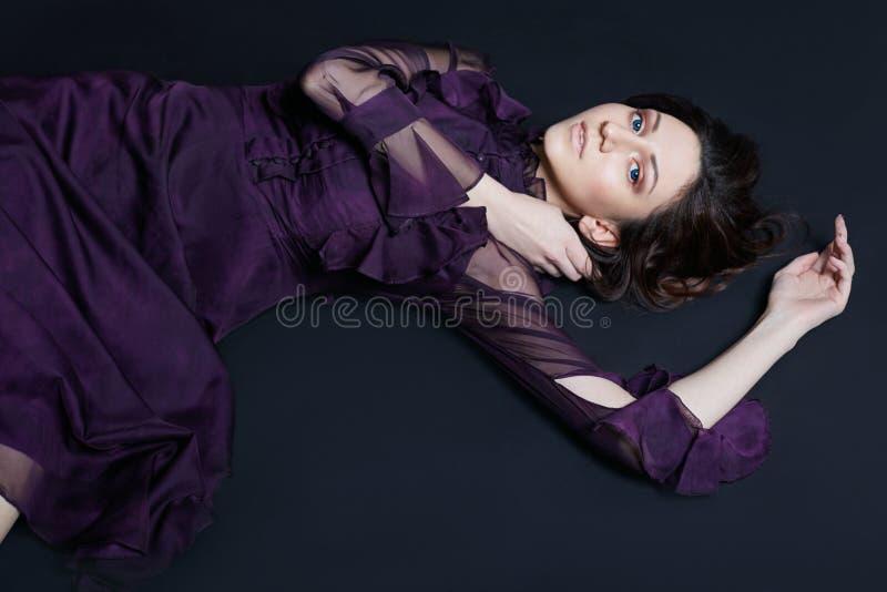 Ponga en contraste el retrato armenio de la mujer de la moda con los ojos azules grandes que mienten en el piso en un vestido púr foto de archivo libre de regalías