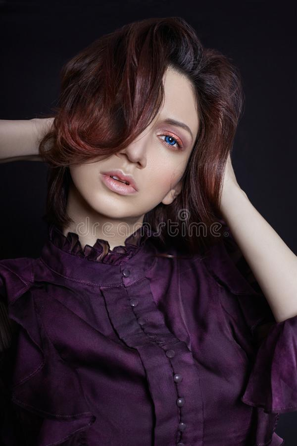 Ponga en contraste el retrato armenio de la mujer de la moda con los ojos azules grandes en un fondo oscuro en un vestido púrpura imágenes de archivo libres de regalías