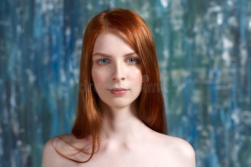 Ponga en contraste el retrato del estudio de una mujer joven con el pelo rojo largo y la piel blanca pura en la cara y los hombro foto de archivo