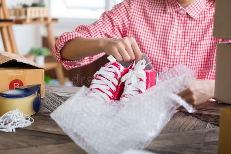 Ponga en marcha los pequeños zapatos del embalaje del propietario de negocio en la caja en el workpl imagen de archivo libre de regalías