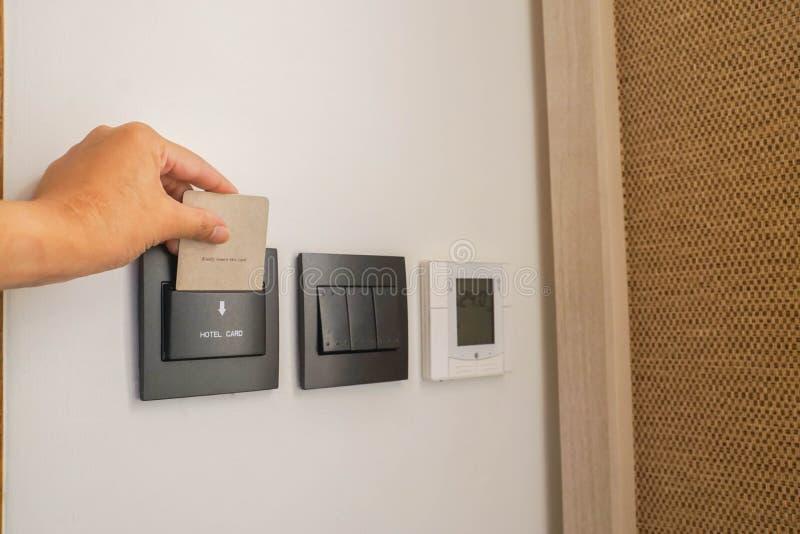 Ponga la llave electrónica del hotel de la mujer en el dormitorio para la electricidad y los dispositivos imágenes de archivo libres de regalías