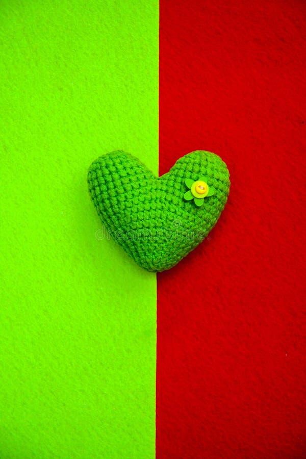 Ponga verde el corazón hecho punto en un fondo verde y rojo, un símbolo del amor para felicitar el día de fiesta imagen de archivo libre de regalías