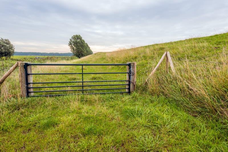 Ponga verde la puerta de acero pintada al lado de un dique holandés fotos de archivo