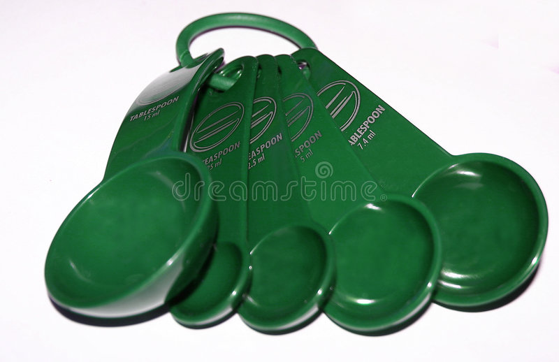 Ponga verde las cucharas dosificadoras fotos de archivo