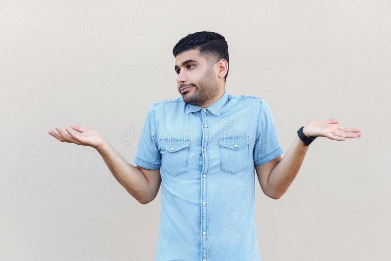 Pongo el `t s? El retrato del hombre barbudo joven hermoso confuso en la situación azul de la camisa con los brazos aumentados y  fotografía de archivo libre de regalías