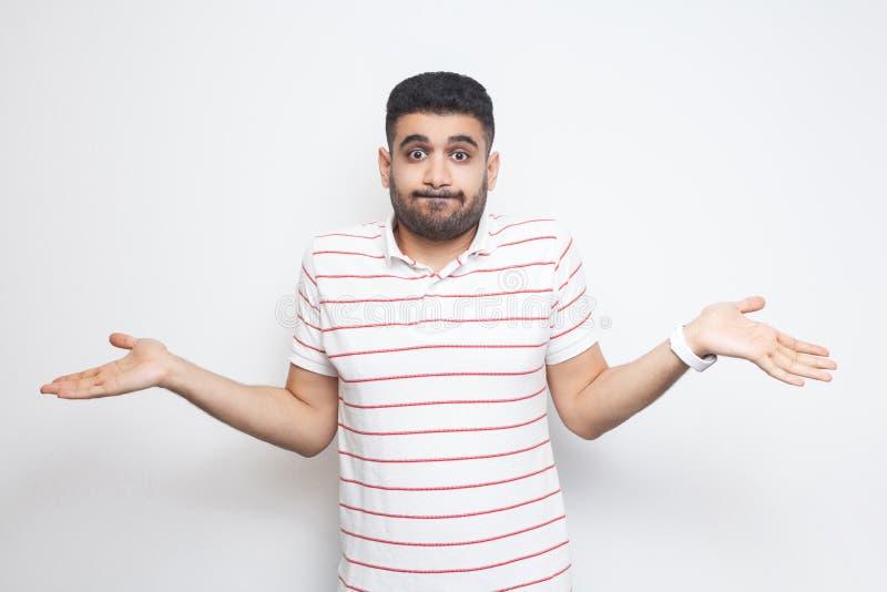 Pongo el `t s? El retrato del hombre joven barbudo hermoso confuso en la situación rayada de la camiseta con los brazos aumentado fotografía de archivo