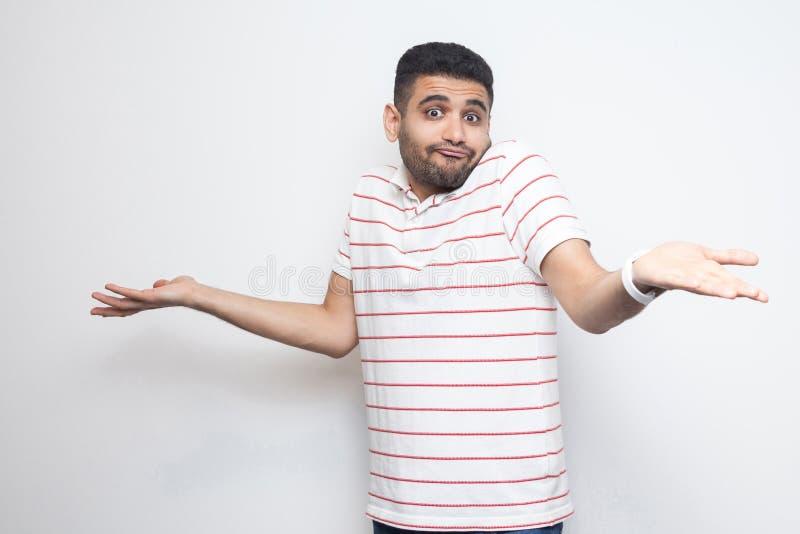 Pongo el `t s? El retrato del hombre joven barbudo hermoso confuso en la situación rayada de la camiseta con los brazos aumentado foto de archivo libre de regalías
