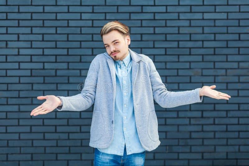 Pongo el `t s? Retrato del hombre rubio joven hermoso descuidado o confuso en el estilo sport que se coloca con los brazos aument imagen de archivo libre de regalías