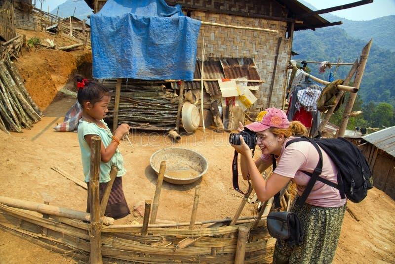 PONGSALI, LAOS - APRIL 2014: Toeristenvrouw die foto stammenjong geitje nemen stock afbeeldingen