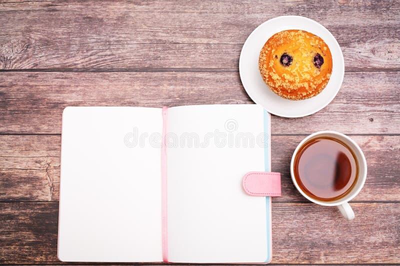 Poniedziałek Rano pojęcie, Gorąca herbata i słodka bułeczka, zasychamy na drewnianym workspace obraz stock