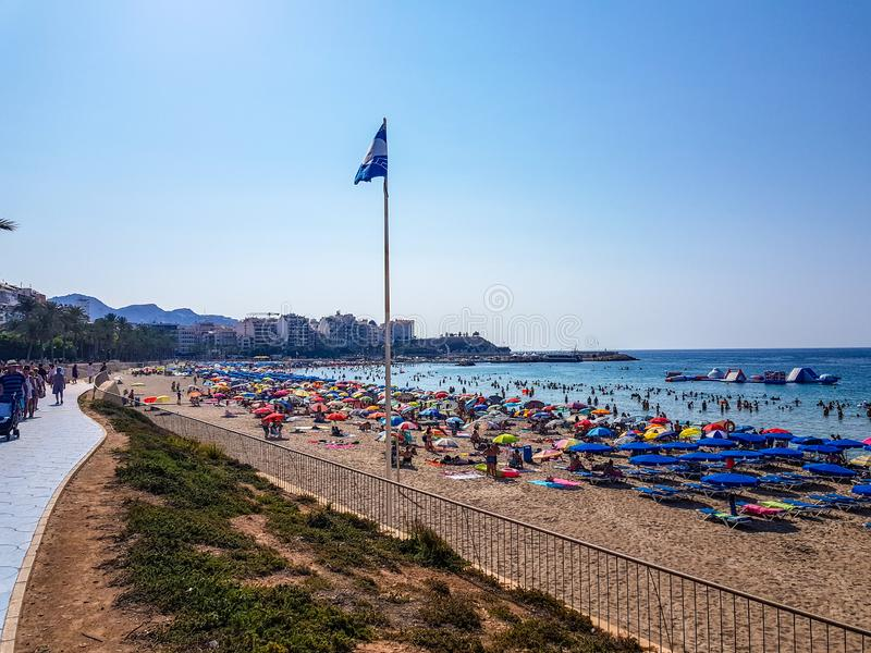 Poniente-Strand von Benidorm im Sommer mit der Flagge, die europäischen blauen Strand der besseren Qualität anzeigt lizenzfreie stockbilder